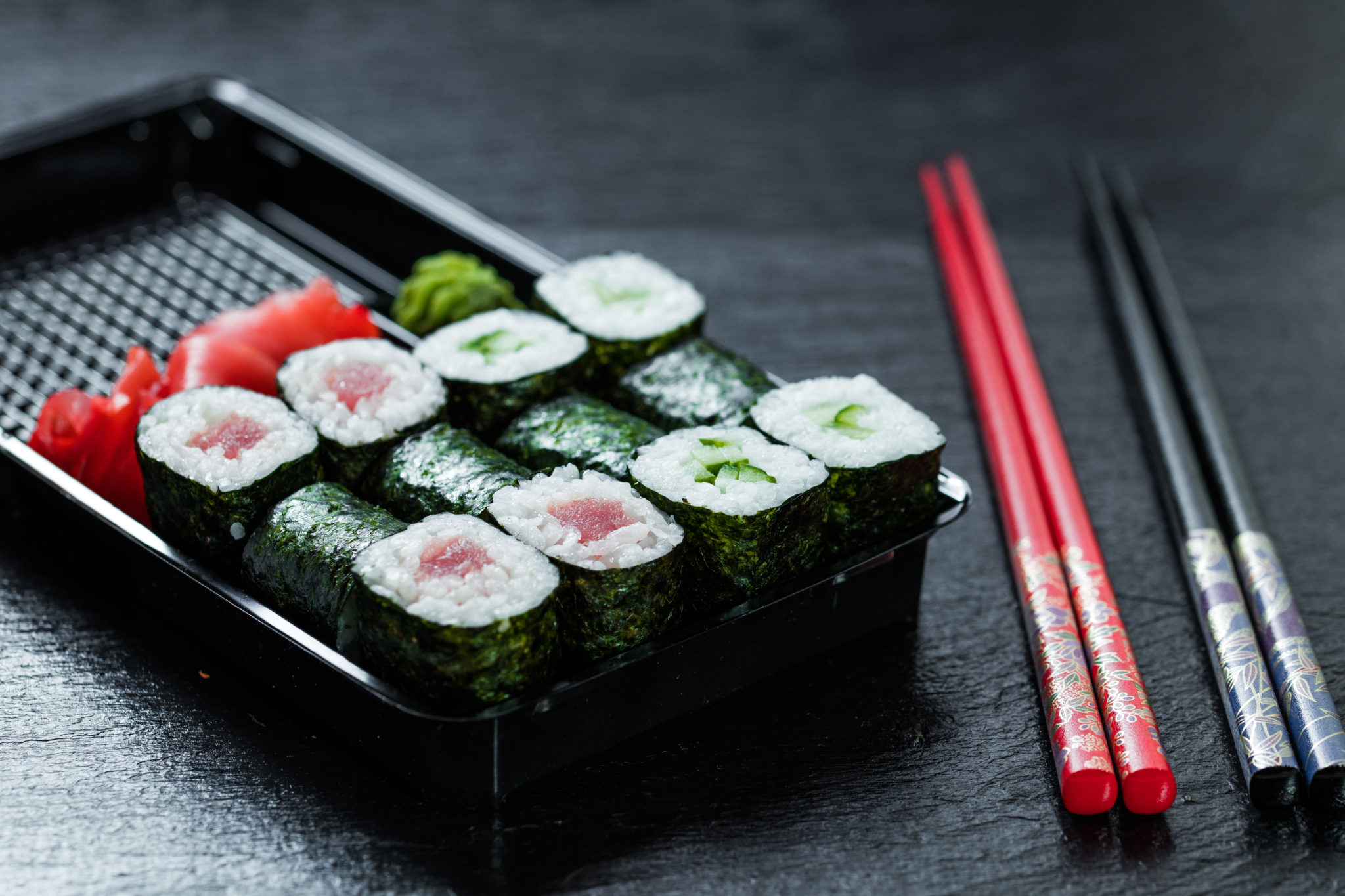 Maki placed in a delivery container next to two pair of chopsticks